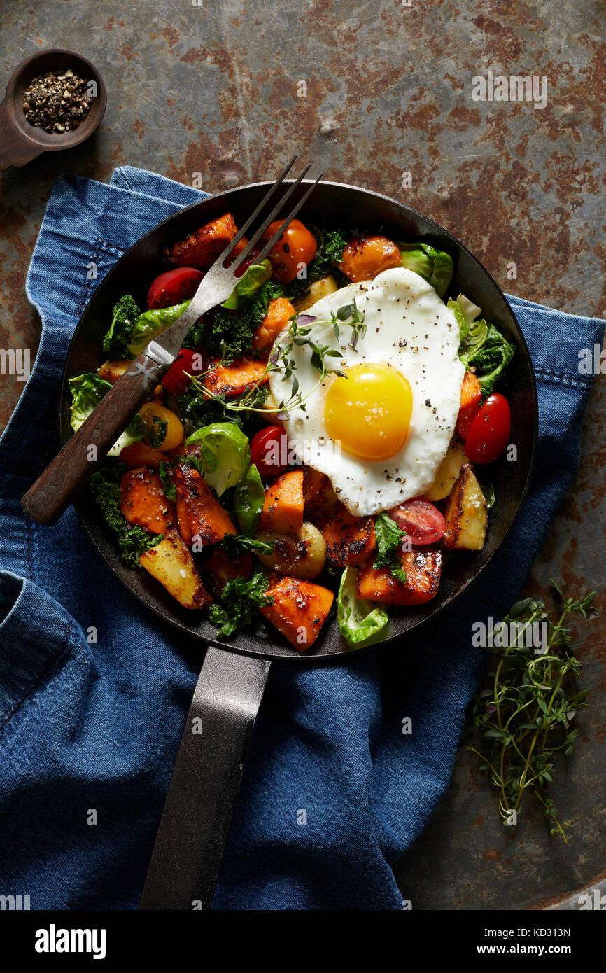 La colazione hash con uovo fritto in padella in ghisa Immagini Stock
