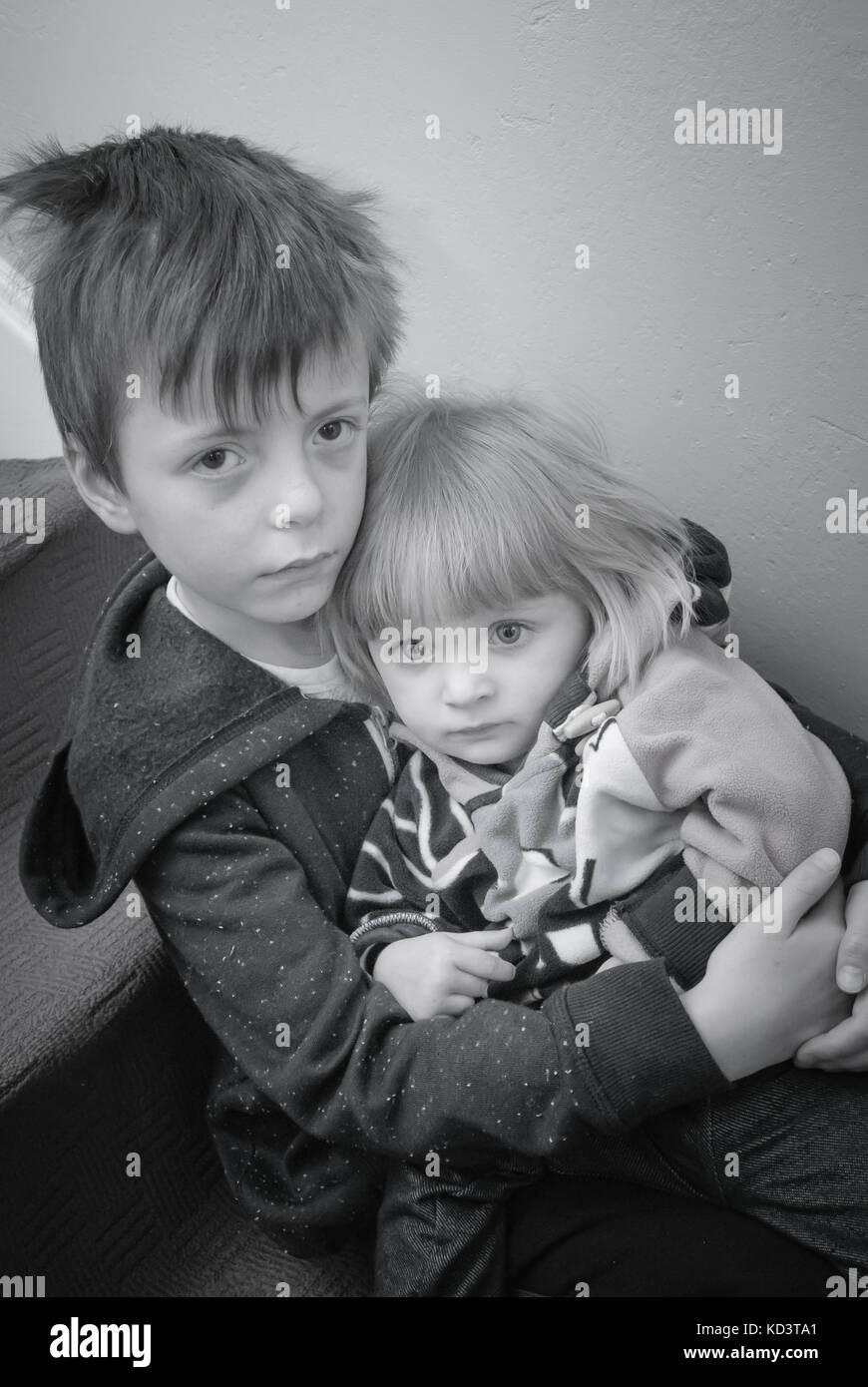 Concettuale di una immagine in bianco e nero di due fratelli che rappresentano una gamma di concetti come la povertà, Immagini Stock