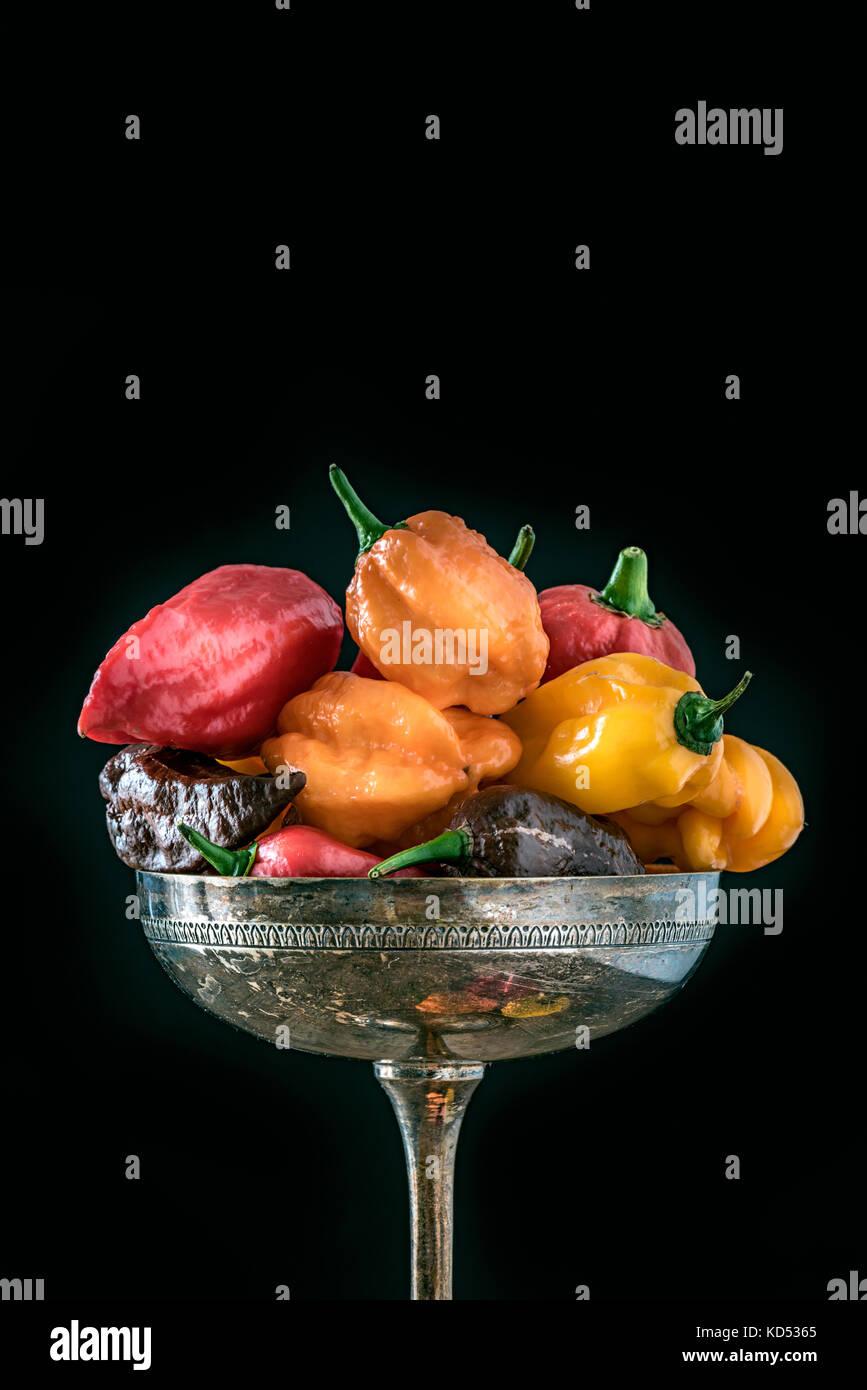 Diversi tipi di peperoncini piccanti su argenteria su sfondo nero copyspace Immagini Stock