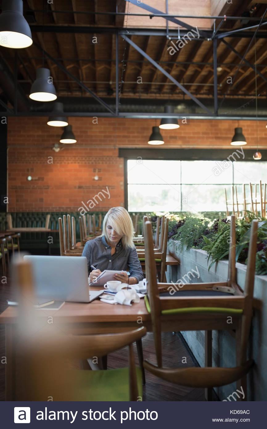 Cafe femmina proprietario di affari pagare le bollette, lavorando al computer portatile Immagini Stock