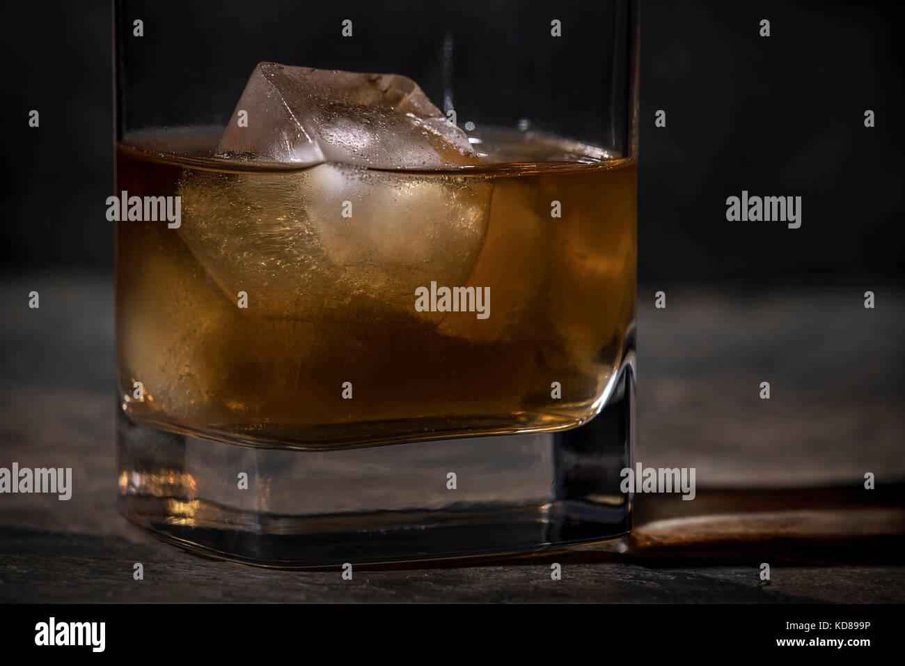 Stretto di ripresa macro di un bicchiere di whisky con 1 grande cubo di ghiaccio in una sfera di bassa del vetro Immagini Stock