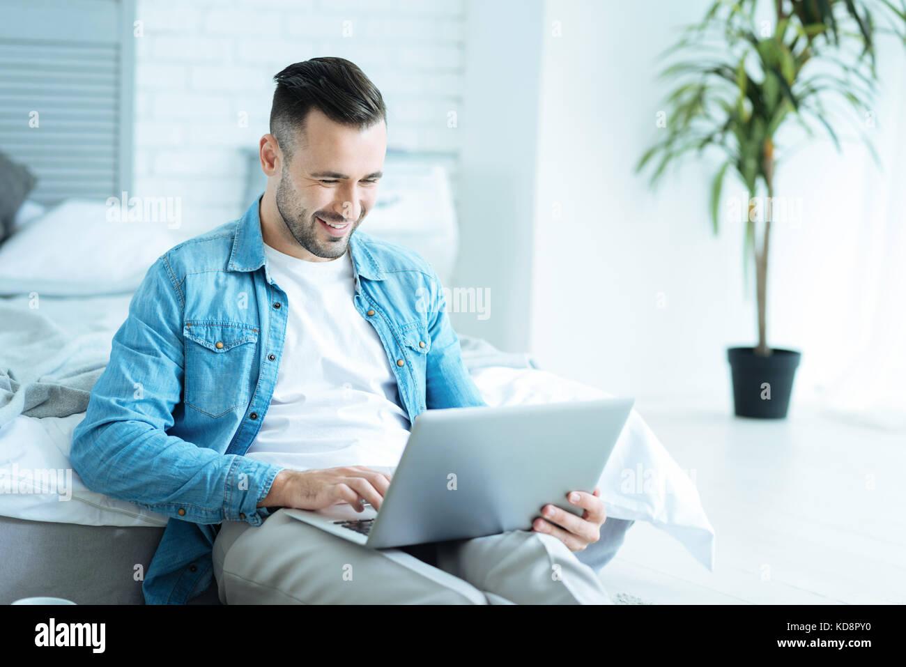 Uomo gioioso grinning ampiamente durante l'utilizzo di laptop Immagini Stock