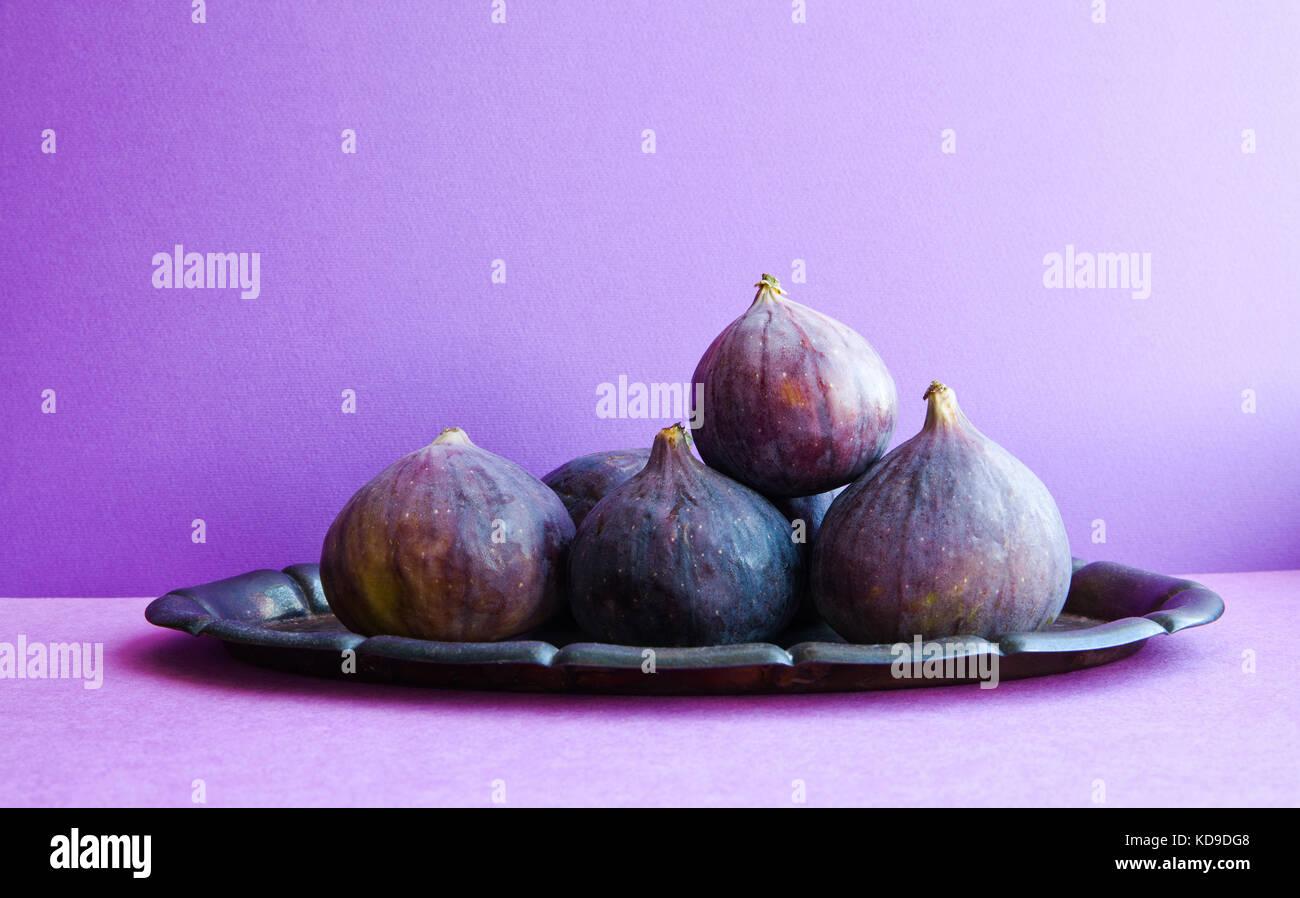 Una sana alimentazione vegetariana concetto. Organici di fig frutti su un vecchio vassoio, bella viola sfondo violetto. Immagini Stock