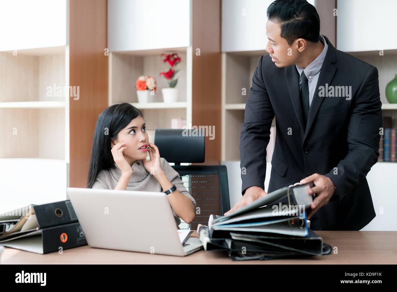 Rabbia imprenditore manager tenendo le cartelle sul suo subordinato tabella. imprenditrice sotto stress a causa Immagini Stock