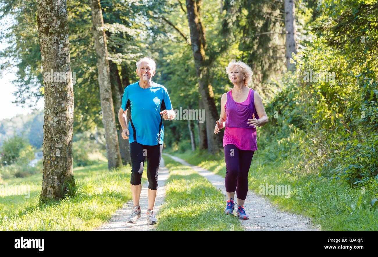 Due anziani attivi con uno stile di vita sano sorridere mentre joggin Immagini Stock