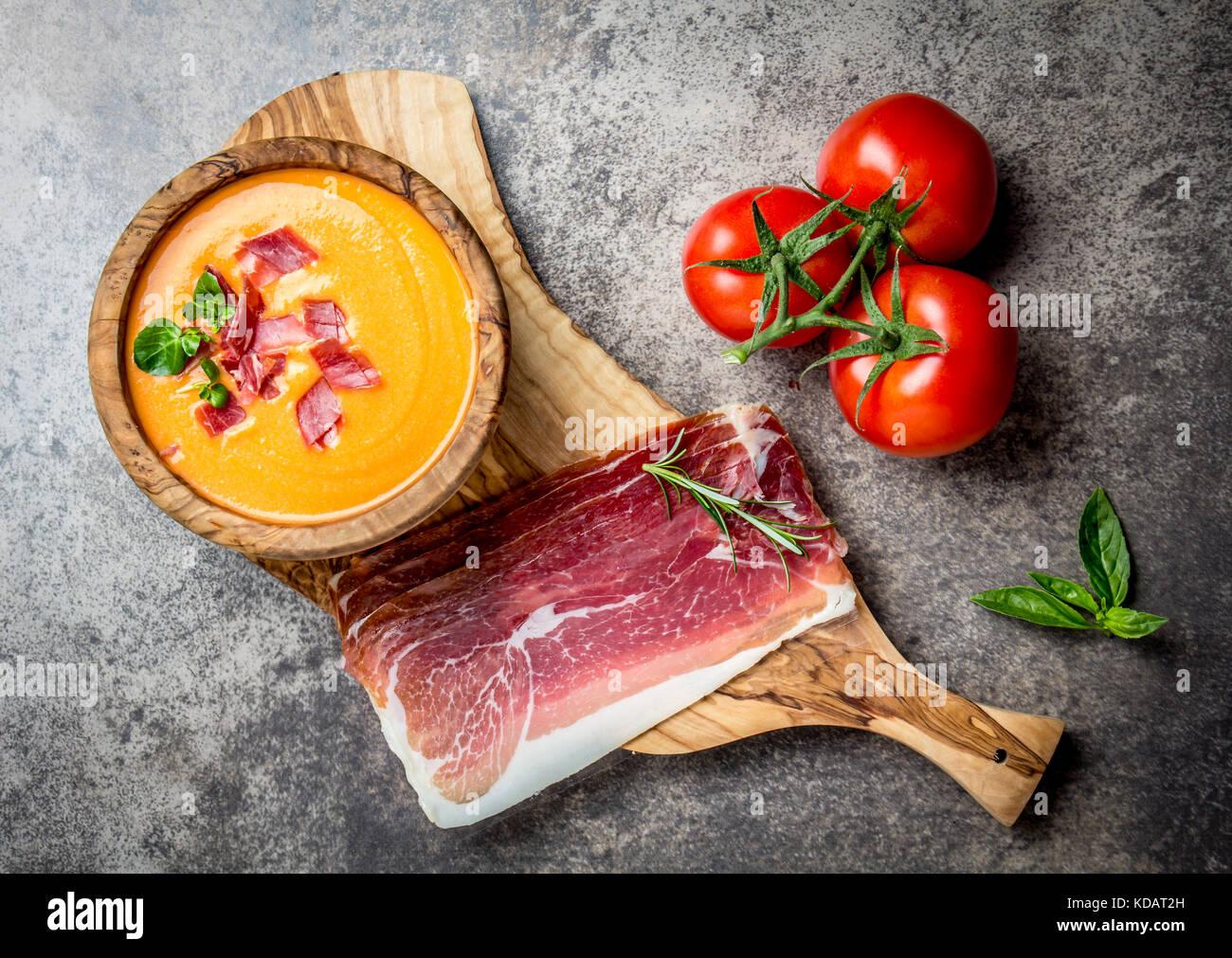 Spagnolo zuppa di pomodoro Salmorejo servita in olive ciotola di legno con prosciutto jamon serrano su sfondo di Immagini Stock
