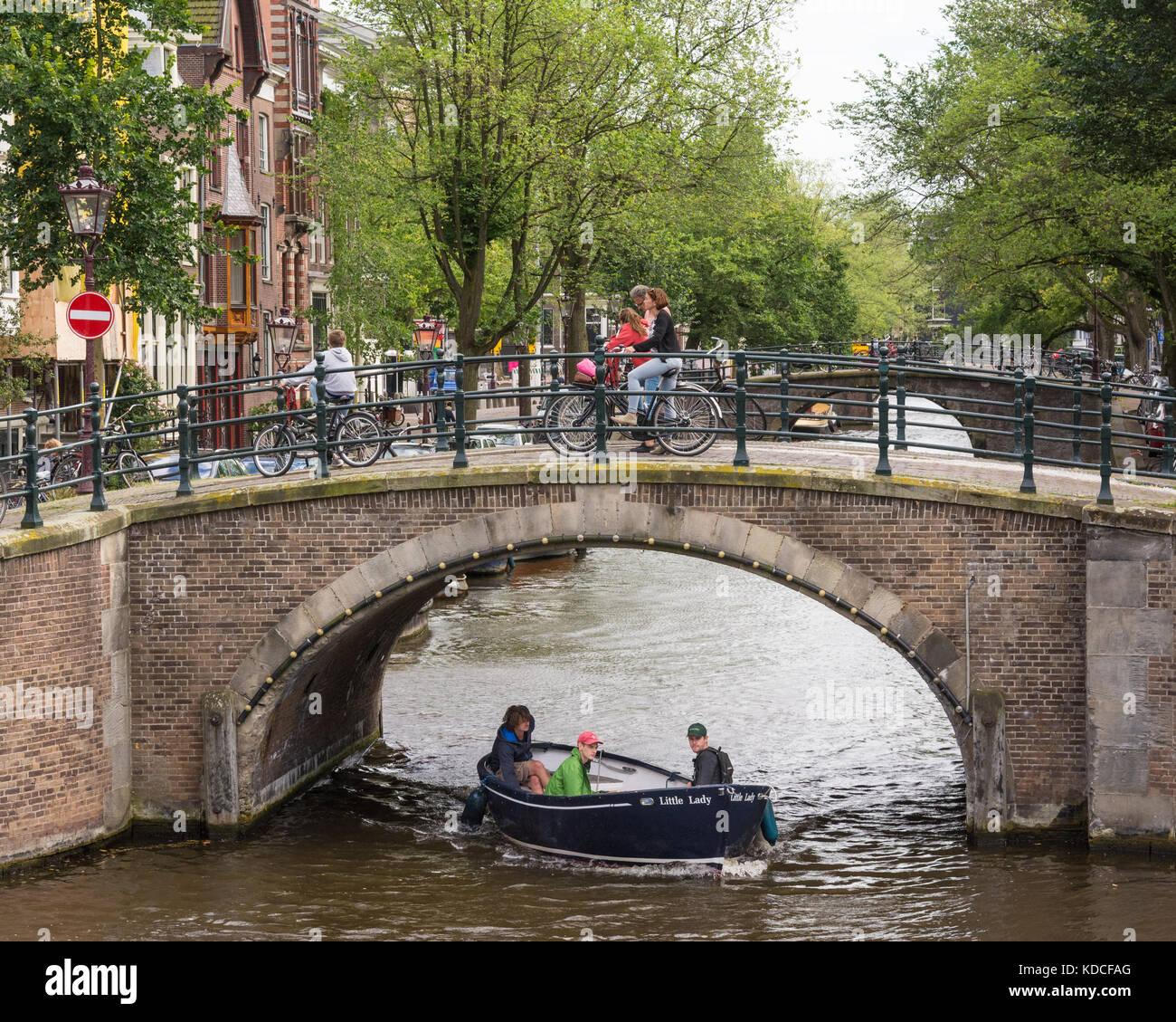 Persone in bicicletta su un ponte sul canale Reguliersgracht ad Amsterdam in Olanda come una piccola barca che passa Foto Stock