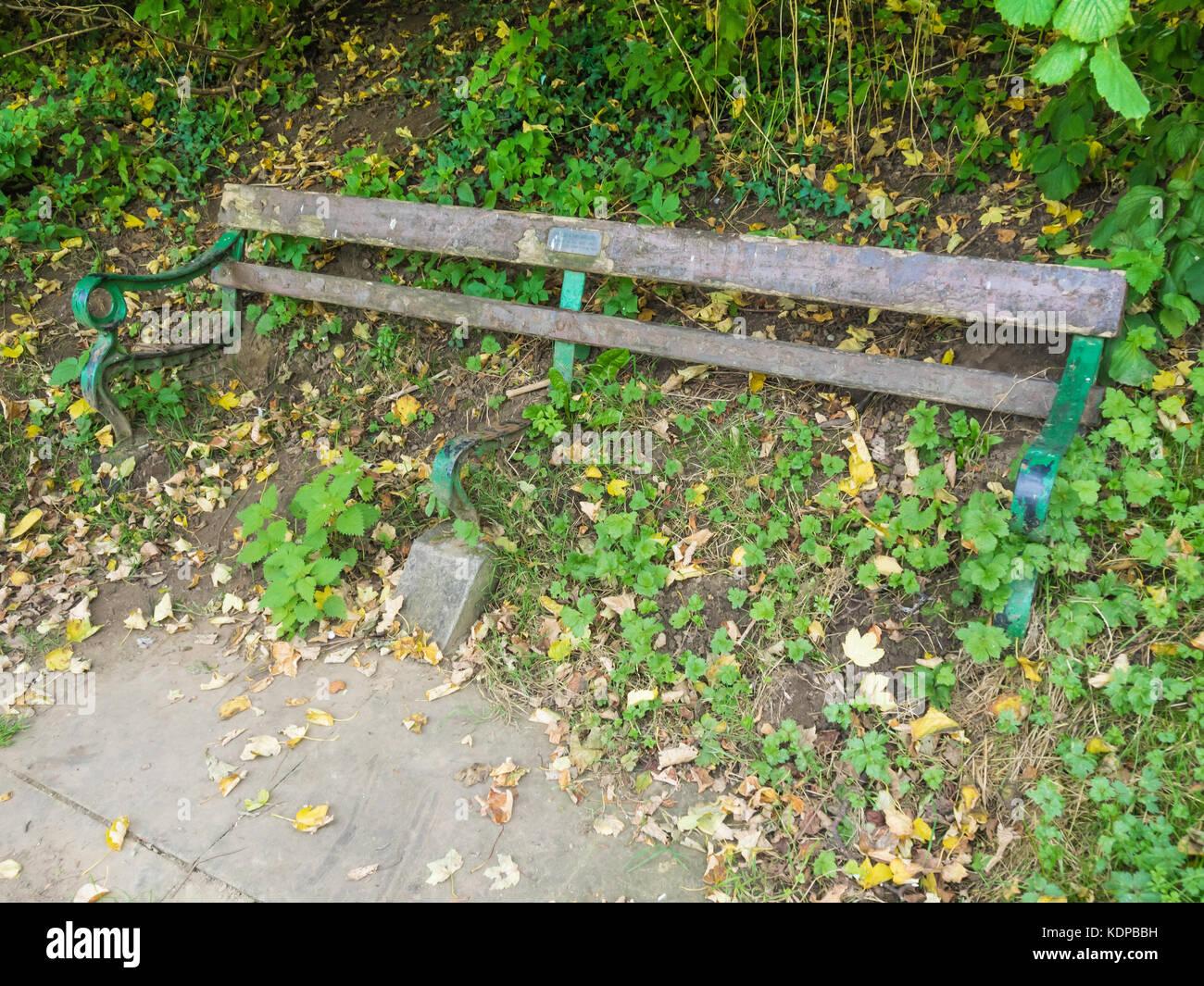 Pubblico sedile unico, con una dedizione ad un giovane che morì nel 1987, con sedile in legno decaduto e perso di lasciare il sedile inutile Foto Stock