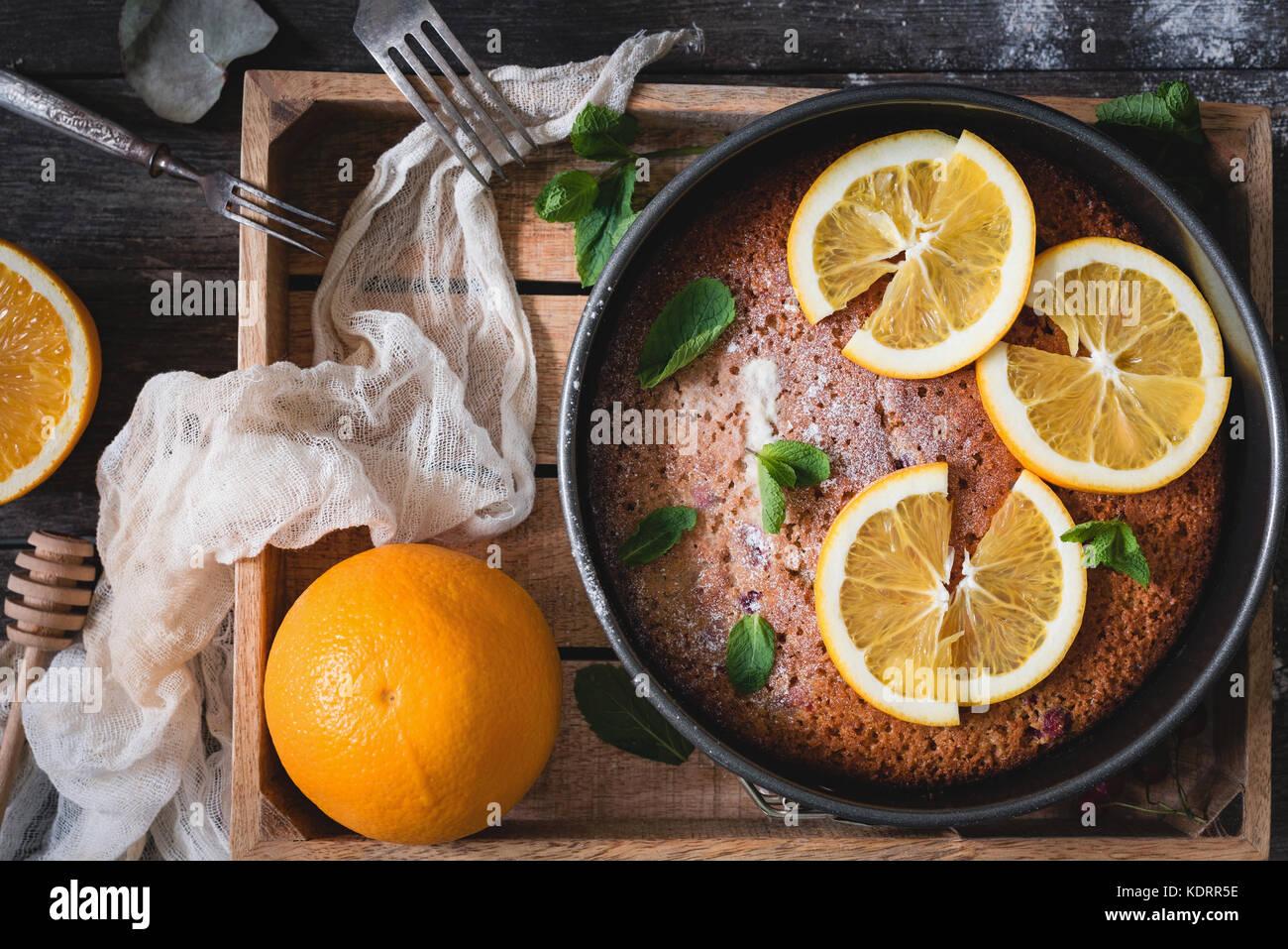 Orange torta decorata con fettine di arancia e foglia di menta sul vassoio in legno vista dall'alto. cibo ancora Immagini Stock
