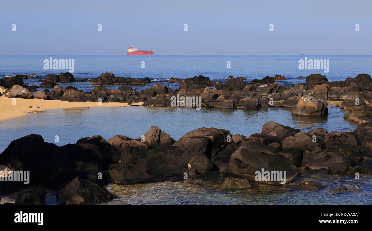 Tranquilla piccola baia con un grande contenitore rosso nave all'orizzonte in formato paesaggio con spazio di Immagini Stock