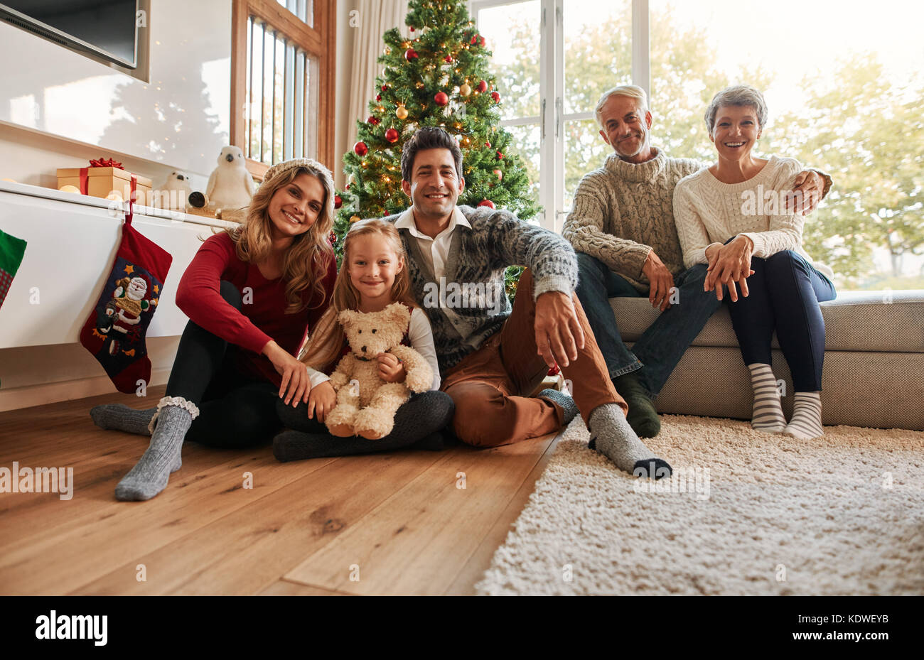 Ritratto di una famiglia felice seduti a casa nel soggiorno. Tre ...