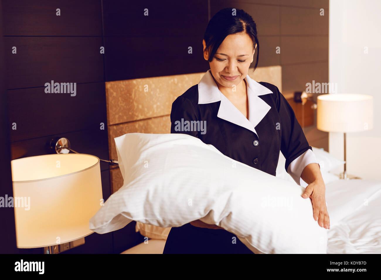 Attento brunette guardando cuscino bianco Foto Stock