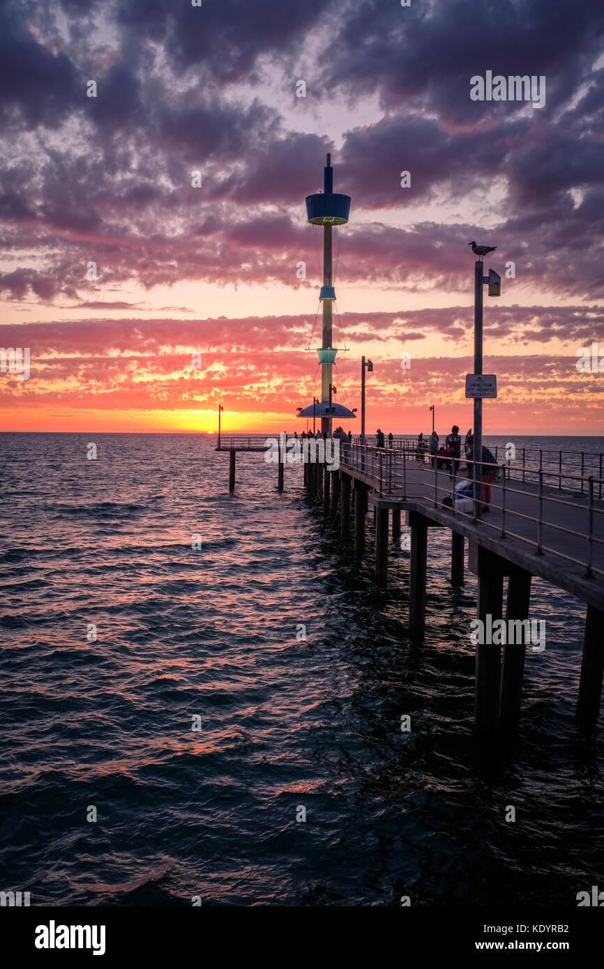 Le persone godono di un magnifico tramonto al mare di adelaide del molo di Brighton su una mite serata d'estate. Immagini Stock