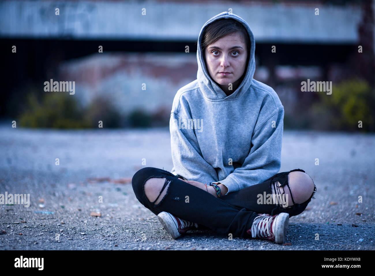 Donna con felpa e pantaloni strappati seduti sulla strada Immagini Stock