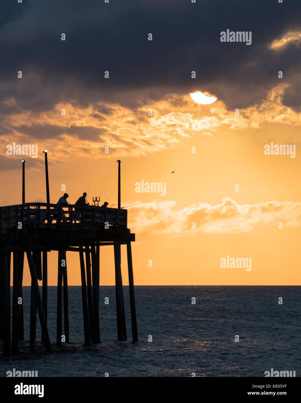 Pescatore per tentare la fortuna poco dopo l'alba a avon molo pesca su hatteras island, North Carolina. Foto Stock