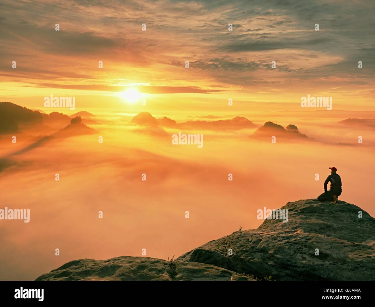 Momento di solitudine su esposta vetta rocciosa. man in black godono di una vista meravigliosa. escursionista sedersi Immagini Stock