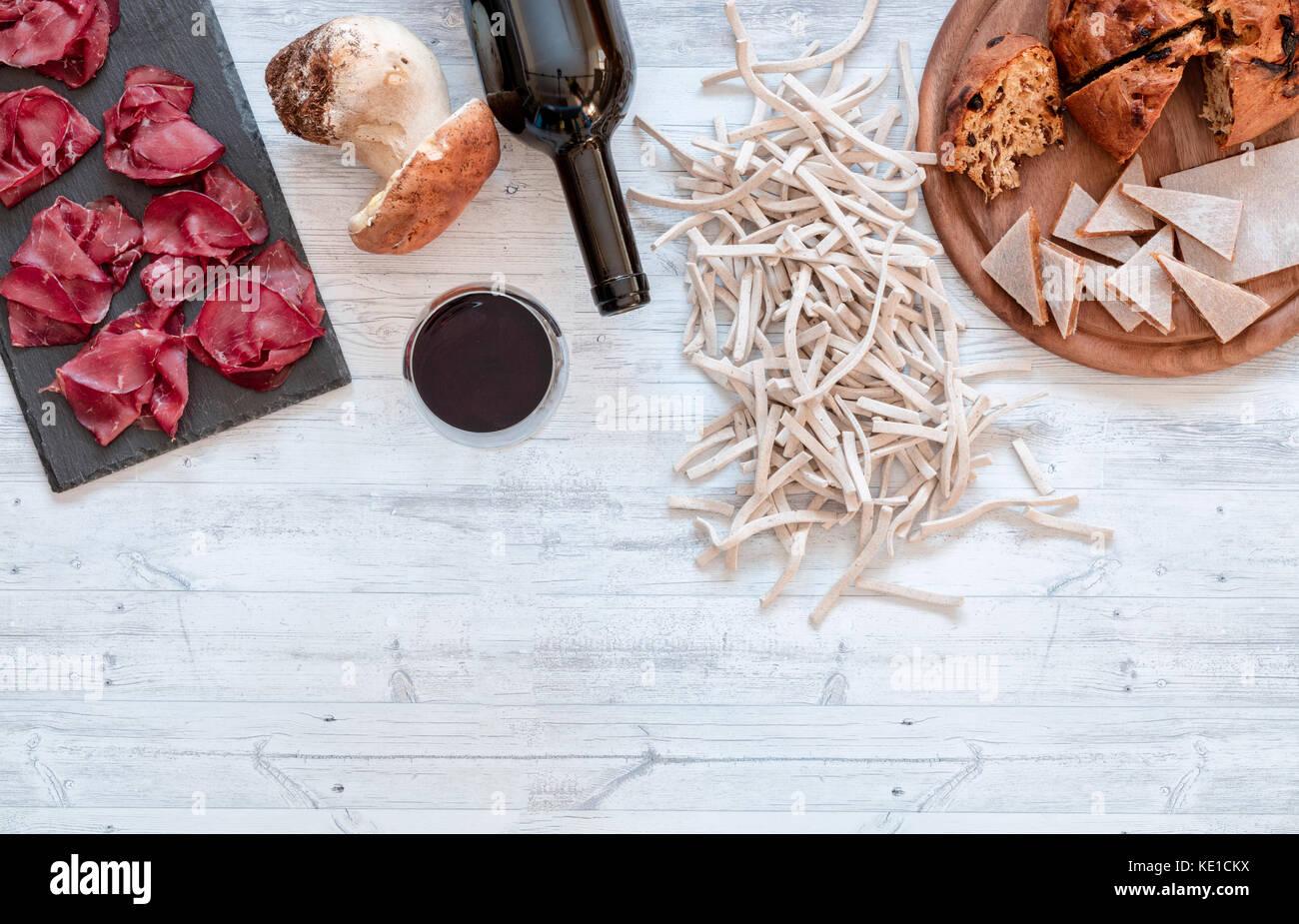 La bresaola igp accompagnato con un bicchiere di vino rosso, pizzoccheri, funghi e besciola, cibo locale della valtellina, Immagini Stock