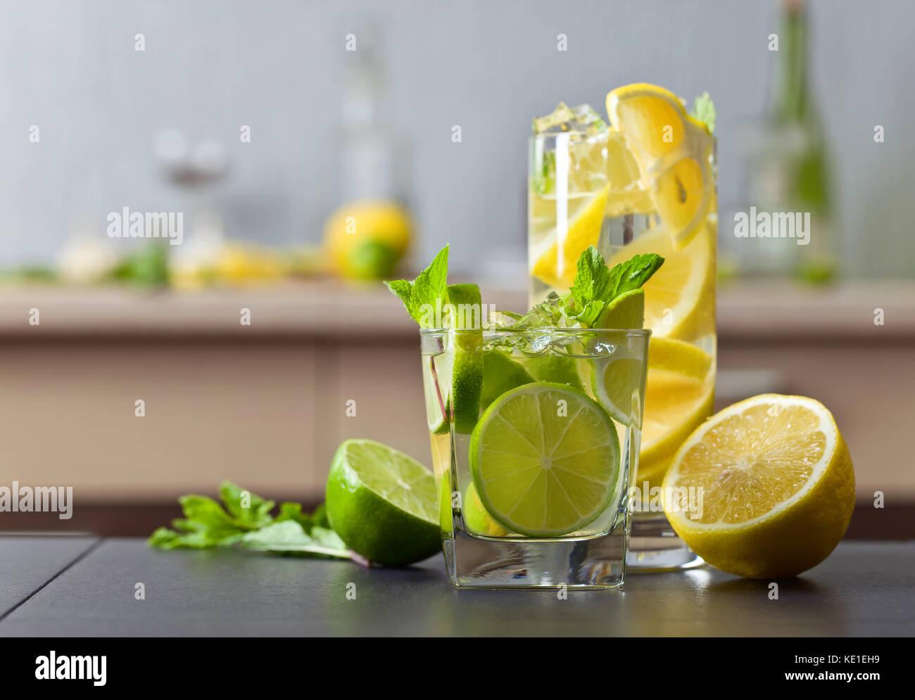 Le bevande con calce , limone e menta piperita su un nero tavolo da cucina . Immagini Stock