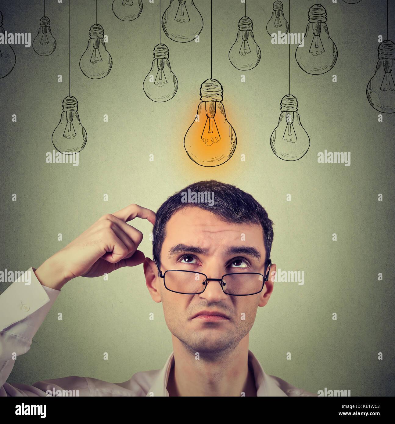 Ritratto di pensare l'uomo in bicchieri cercando con luce idea lampadina sopra la testa isolata sul muro grigio Immagini Stock