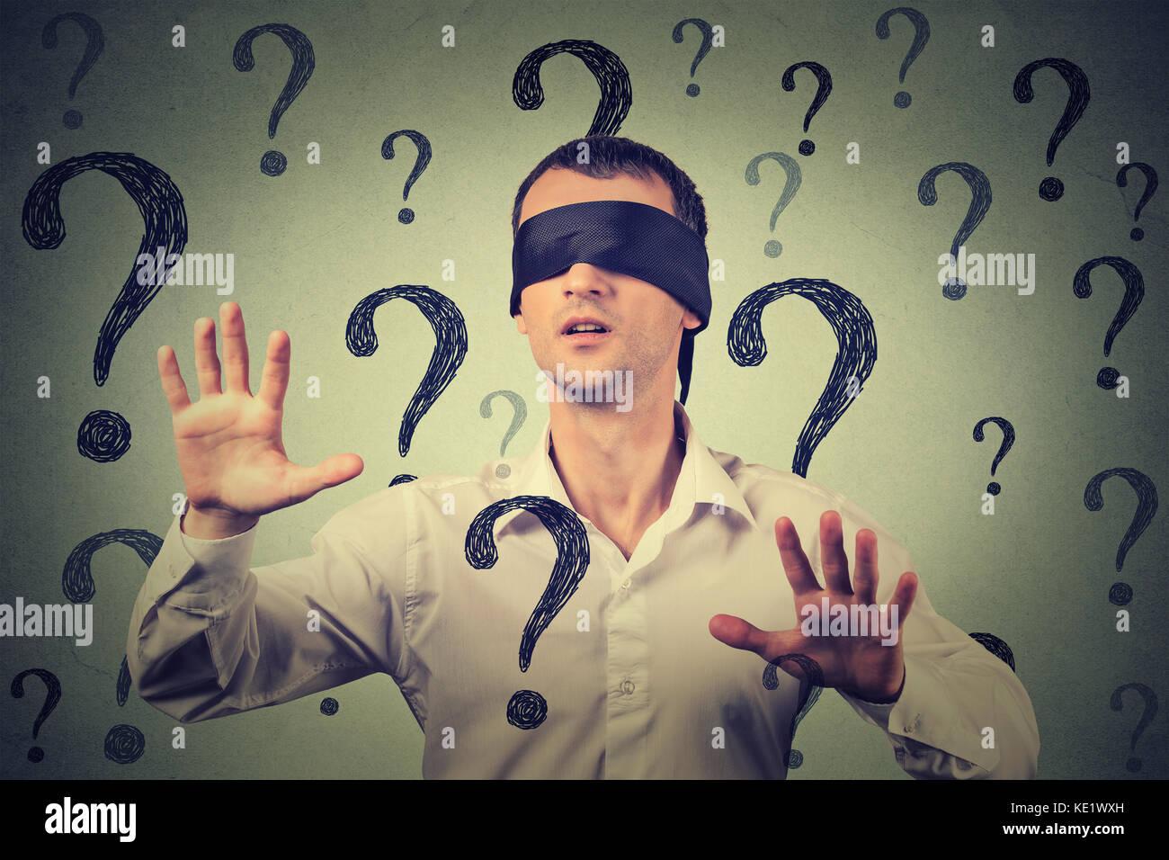 Ritratto a occhi bendati uomo stretching braccia fuori a piedi attraverso molti punti interrogativi Immagini Stock