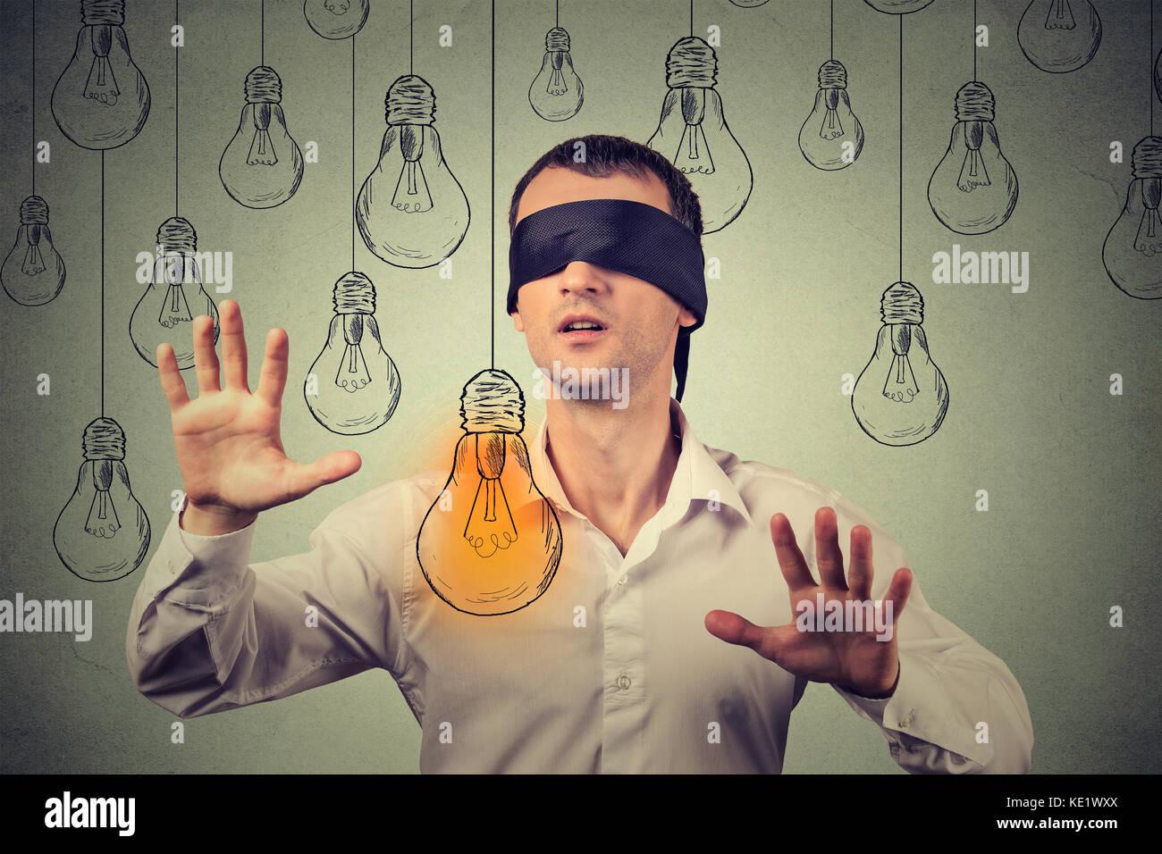 Gli occhi bendati giovane uomo a piedi attraverso le lampadine alla ricerca per la brillante idea Immagini Stock