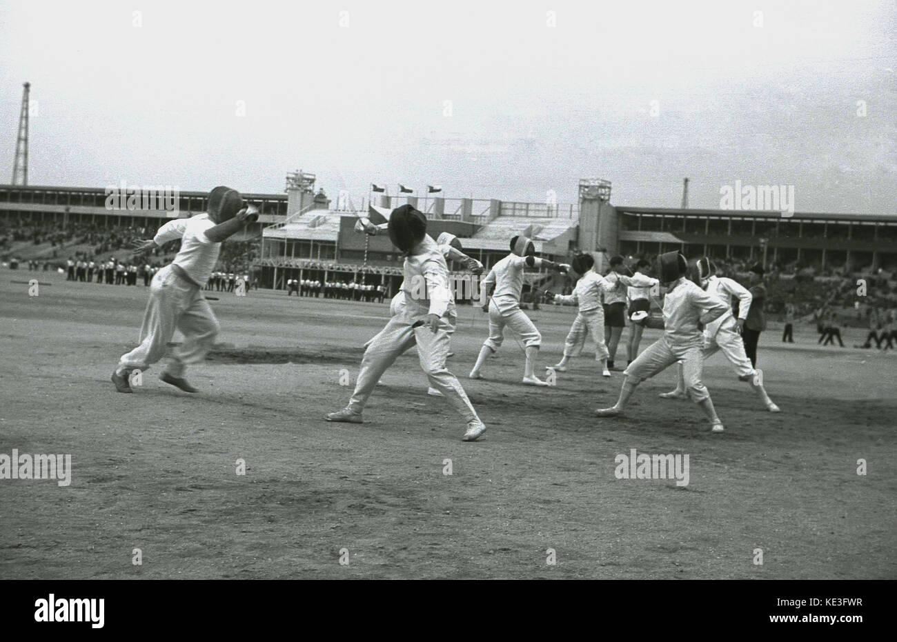 1938 storico, maschio competitiors scherma nel centro del gigante Strahov Stadium, Praga, Cecoslovacchia al Pan Immagini Stock
