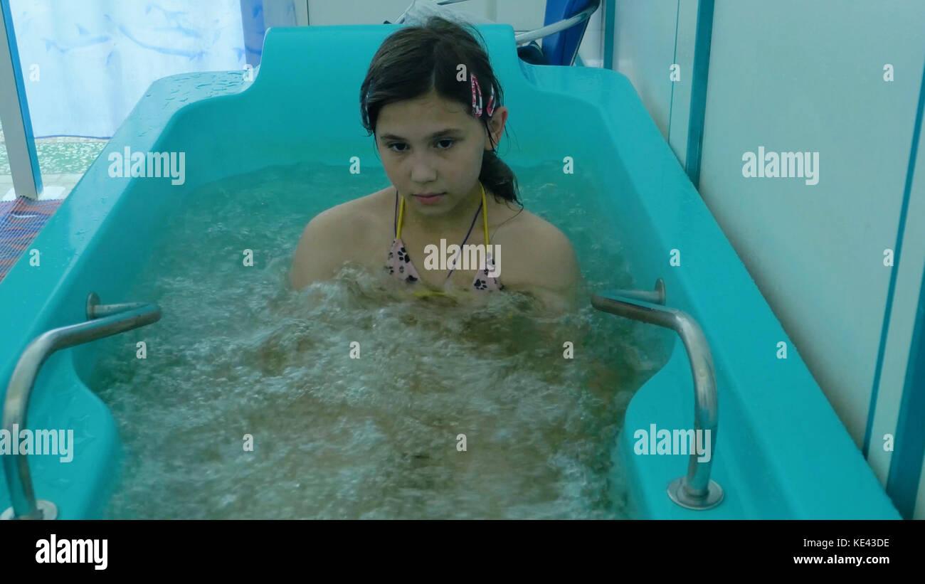 Bella ragazza di balneazione in una vasca da bagno in una spa salute ...