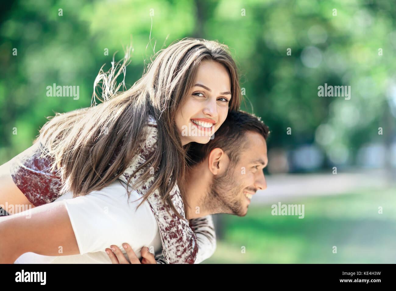 All'esterno ritratto di felici gli amanti del giovane uomo e donna che guarda la fotocamera. Ragazza sorridente Immagini Stock