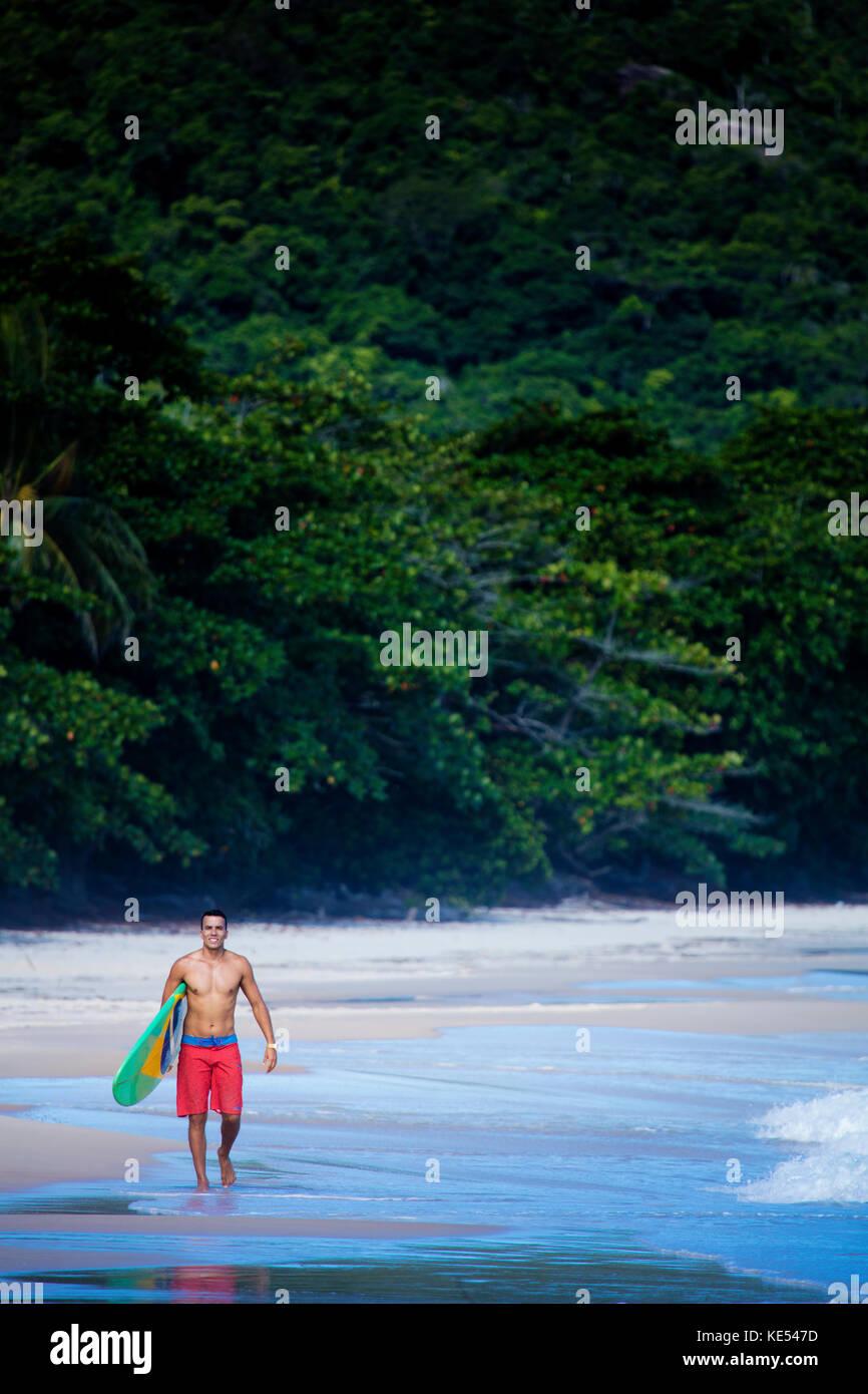 Surfer sulla spiaggia incontaminata in stato di Rio de Janeiro, portando la sua pensione, che mostra una bandiera Immagini Stock