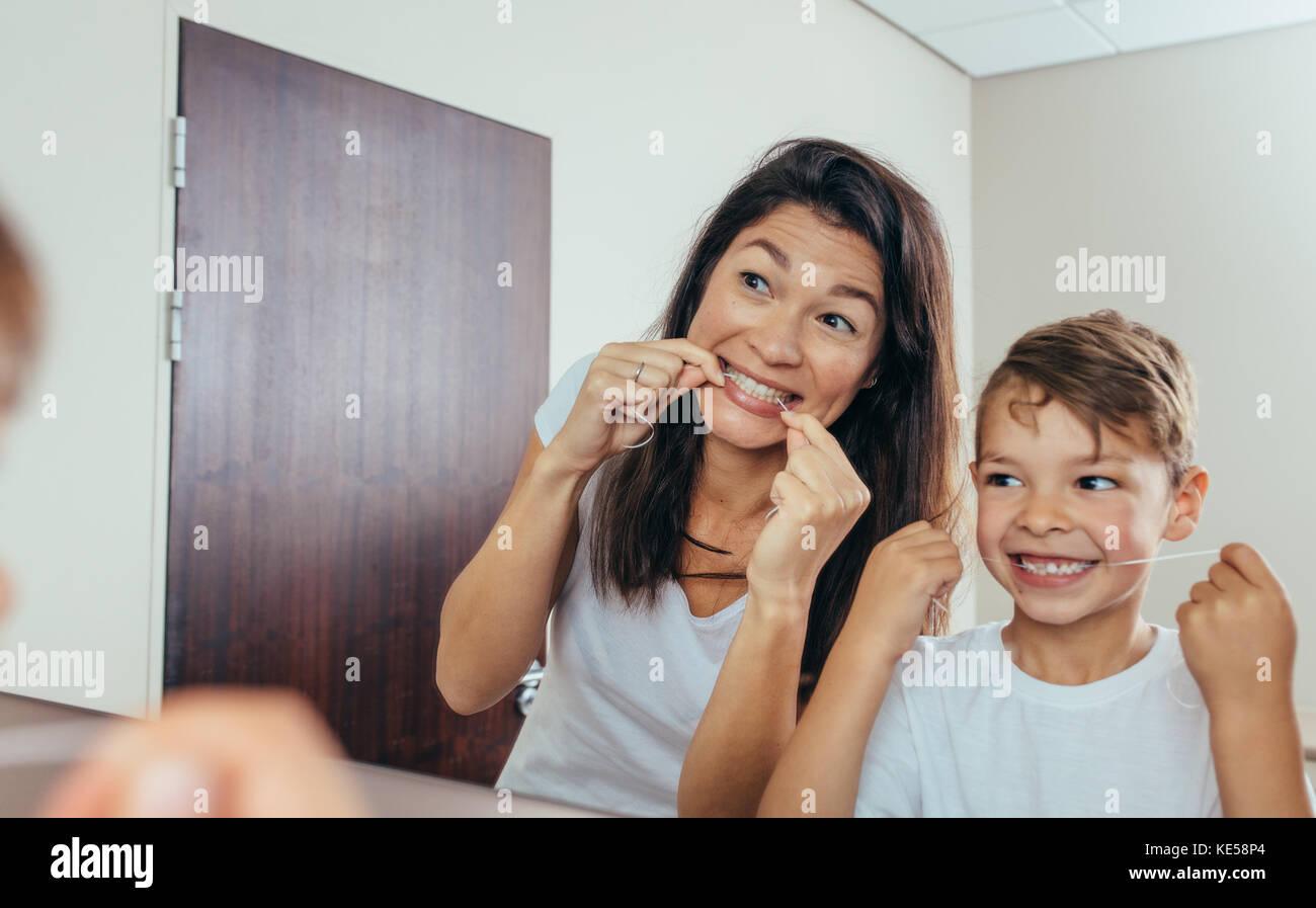 Bambino con sua madre in bagno pulire i denti con filo interdentale. Donna con figlio guardando in uno specchio Immagini Stock