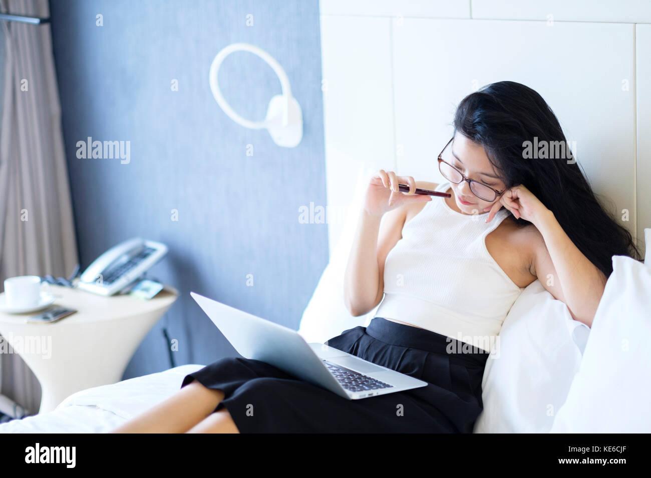 Giovani Asian business donna che lavorano nella sua camera di albergo Immagini Stock