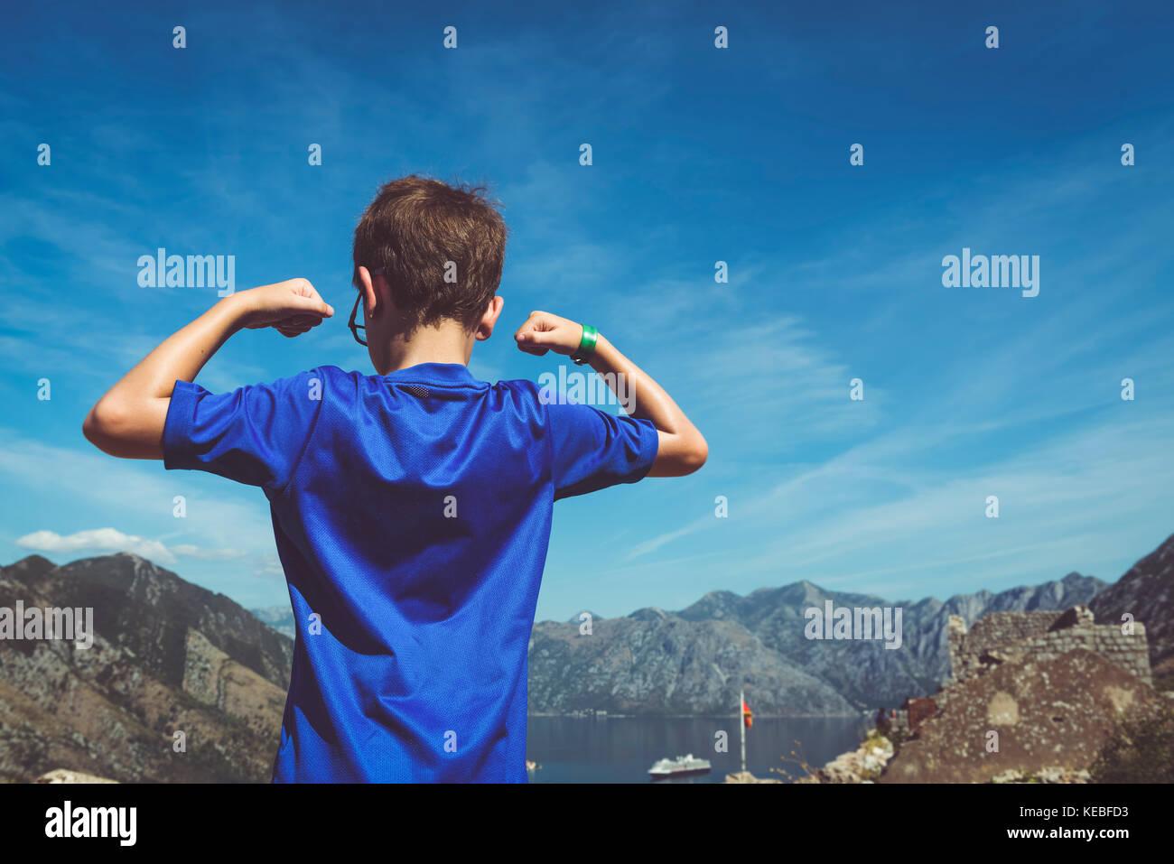 La vista dal forte al di sopra di Kotor dopo una lunga salita con un ragazzo in primo piano mostra i suoi muscoli Immagini Stock