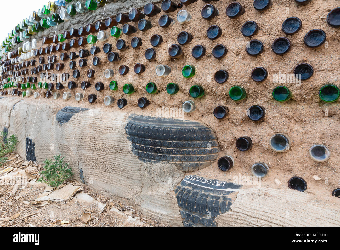 Le bottiglie di vetro e utilizzati pneumatici utilizzati nella costruzione di parete earthship, mondo superiore Immagini Stock