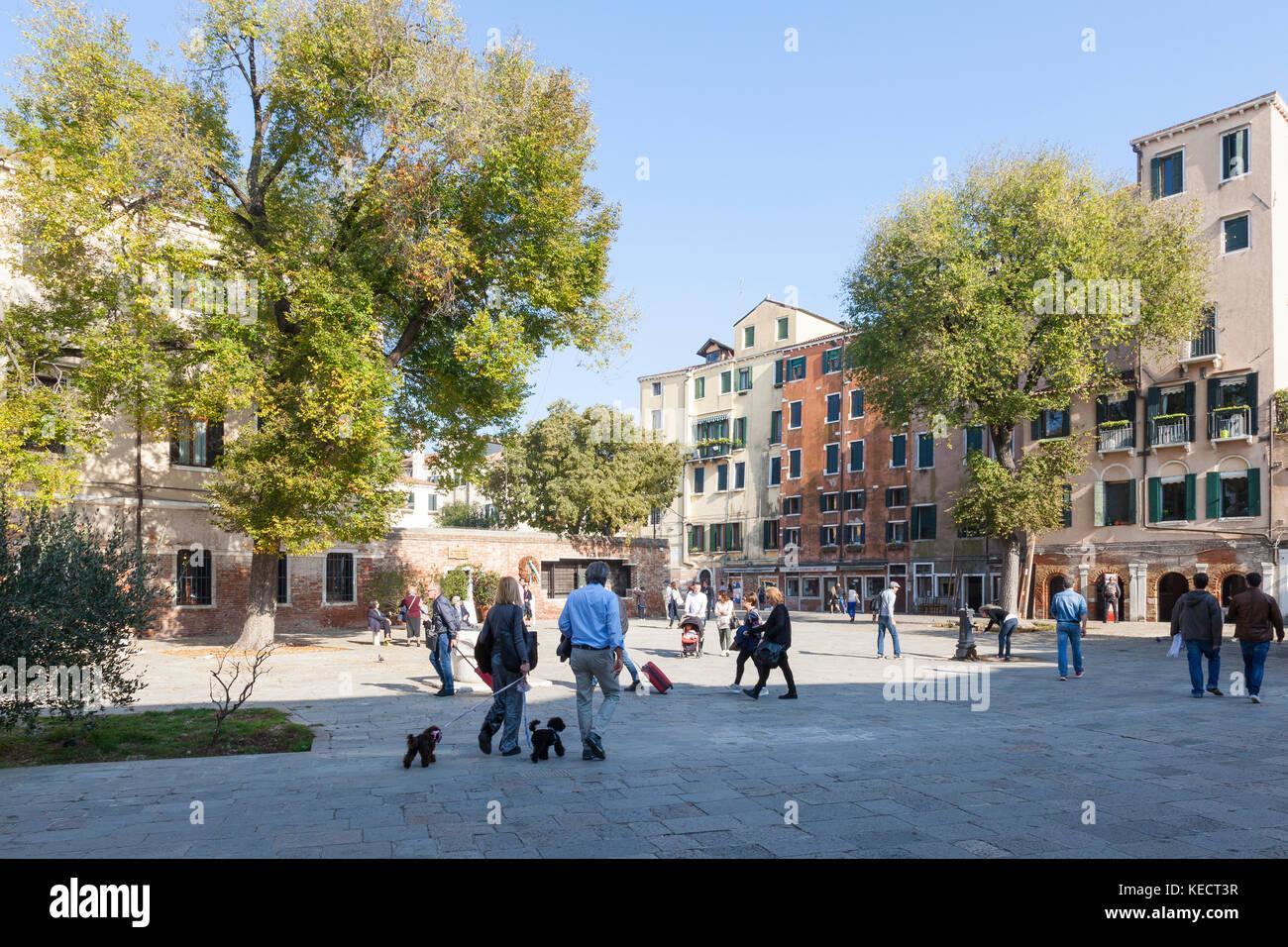 La gente del posto andando sulla loro vita quotidiana e a pochi turisti nel ghetto ebraico nel Campo De Ghetto Novo, Immagini Stock
