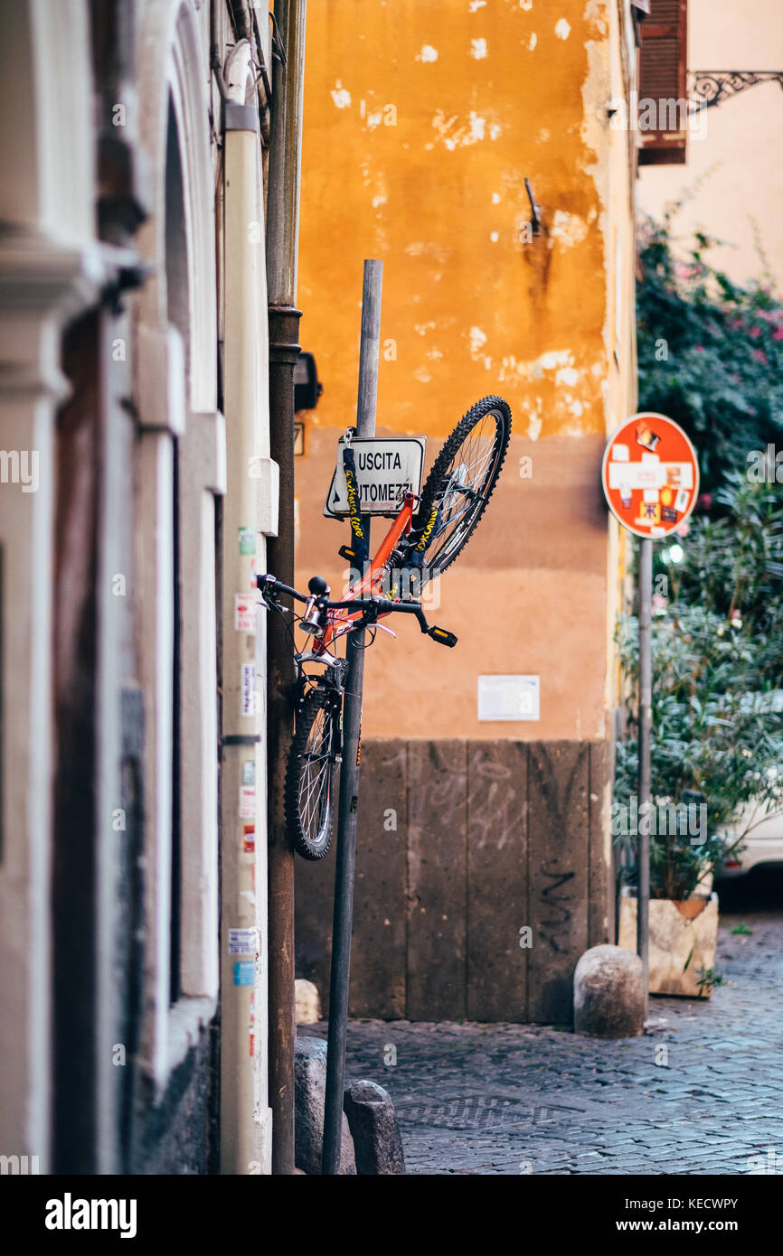 Una bicicletta danneggiata sollevata su un cartello, nel quartiere di Trastevere a Roma, Italia Immagini Stock