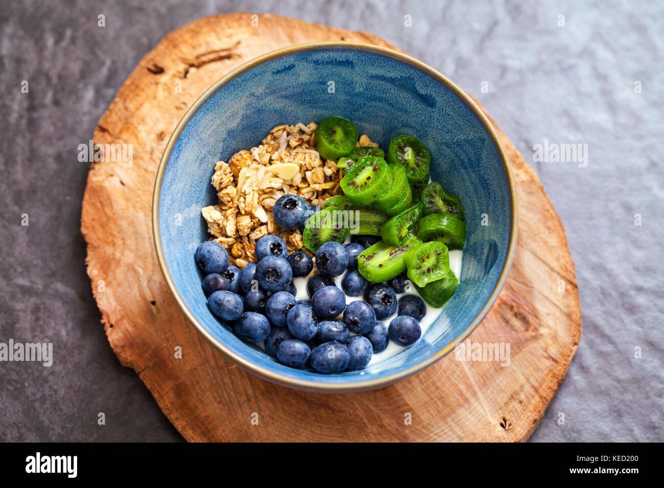 Yogurt con frutti di bosco kiwi, mirtilli e granola Immagini Stock