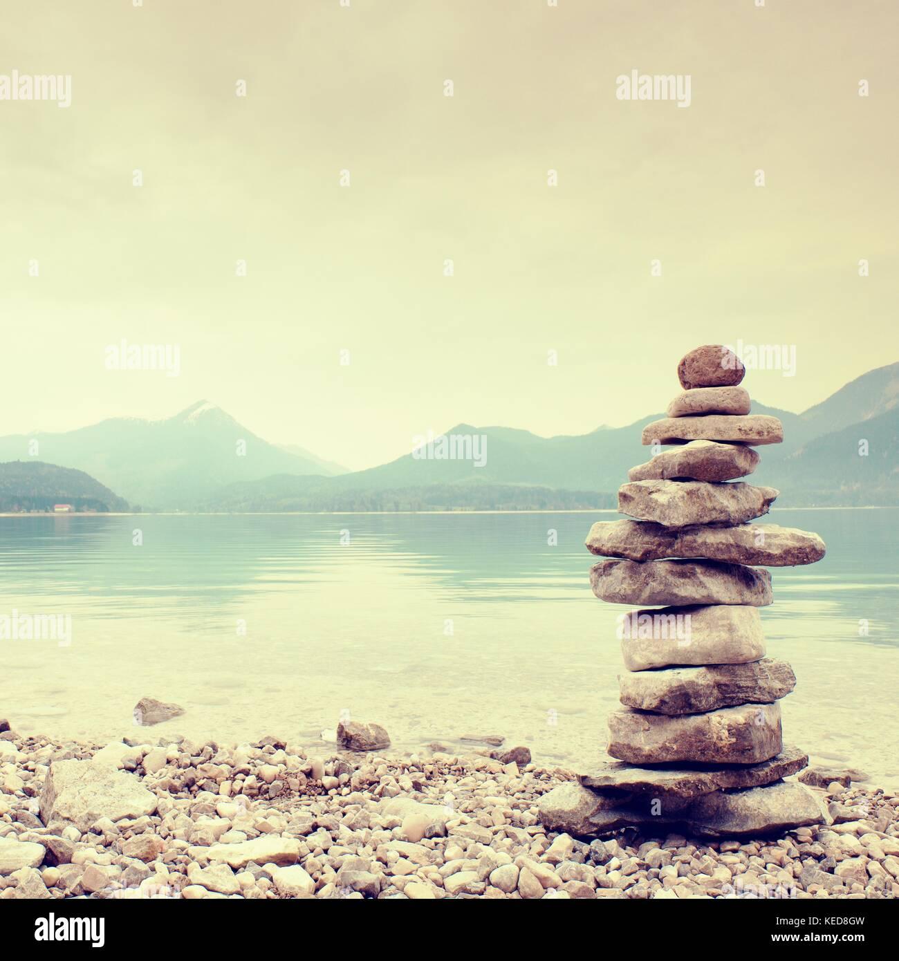 Equilibrato piramide di pietra per memoria. sassoso shore d'acqua blu del lago di montagna con specchio di livello. Immagini Stock