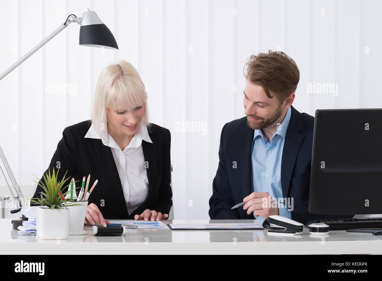 Due imprenditori analizzando il grafico insieme in ufficio Immagini Stock