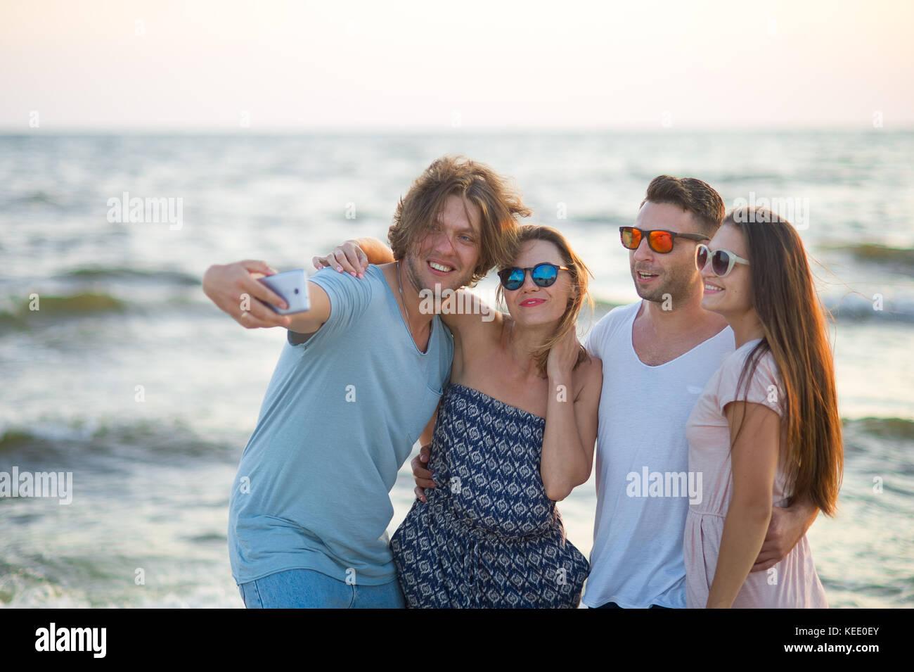 Il Gruppo Di Allegro Giovani Fotografato Sulla Spiaggia Due Ragazzi