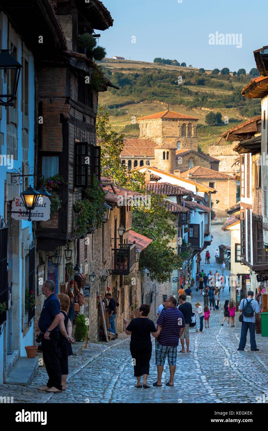 I turisti a piedi passato edifici medievali lungo la strada di ciottoli di calle del cantone in santillana del mar Immagini Stock