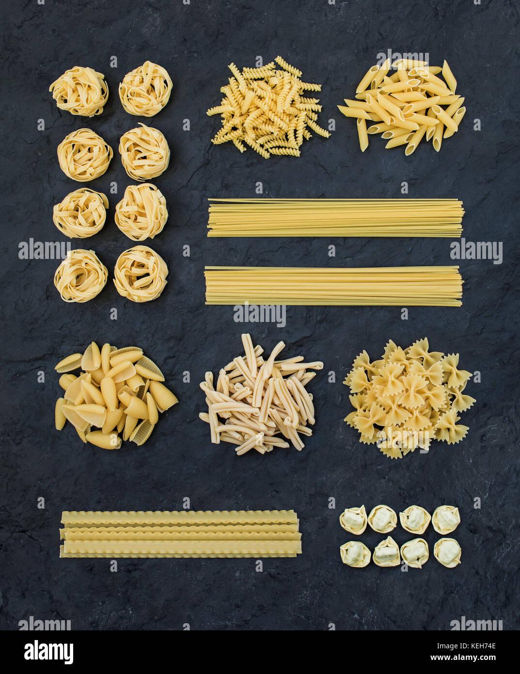 Diversi tipi di italiano di pasta cruda in ardesia nera sullo sfondo di pietra vista dall 39 alto - Diversi tipi di figa ...