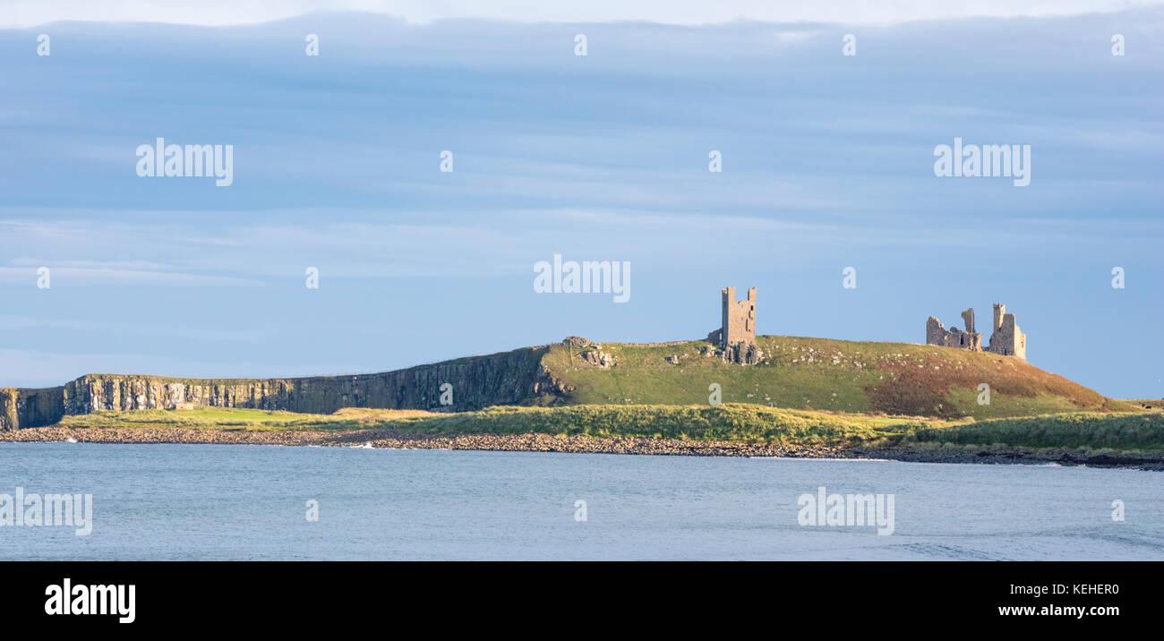 Luce della Sera oltre il castello di Dunstanburgh, Northumberland, England, Regno Unito Foto Stock