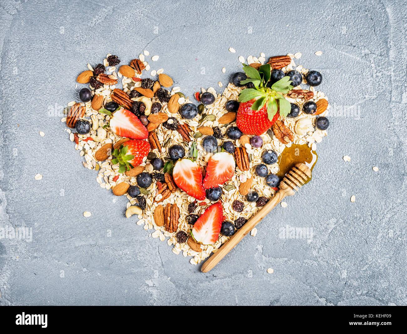 Ingredienti per la cottura di una sana prima colazione in forma di cuore le fragole, mirtilli, dadi, fiocchi d'avena, Immagini Stock