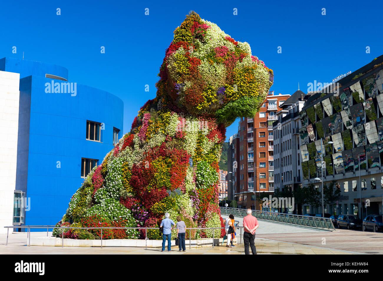 I turisti al cucciolo di Jeff Koons arte floreale in forma di cane al museo Guggenheim dal Silken Gran Hotel Domine Immagini Stock