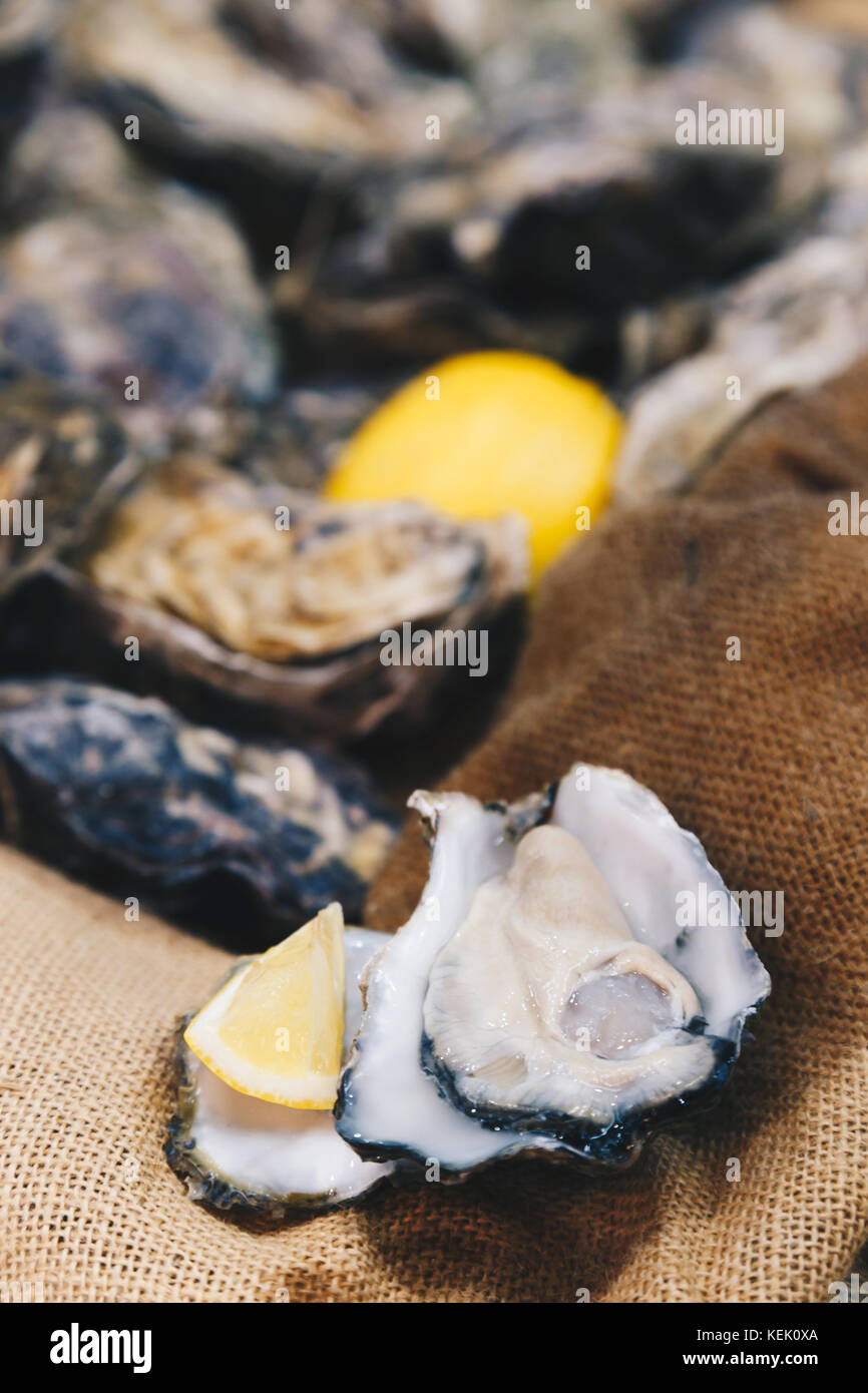 Ostriche fresche in guscio e pezzo di limone pronto a servire sul panno del sacco sacco background. messa a fuoco Immagini Stock