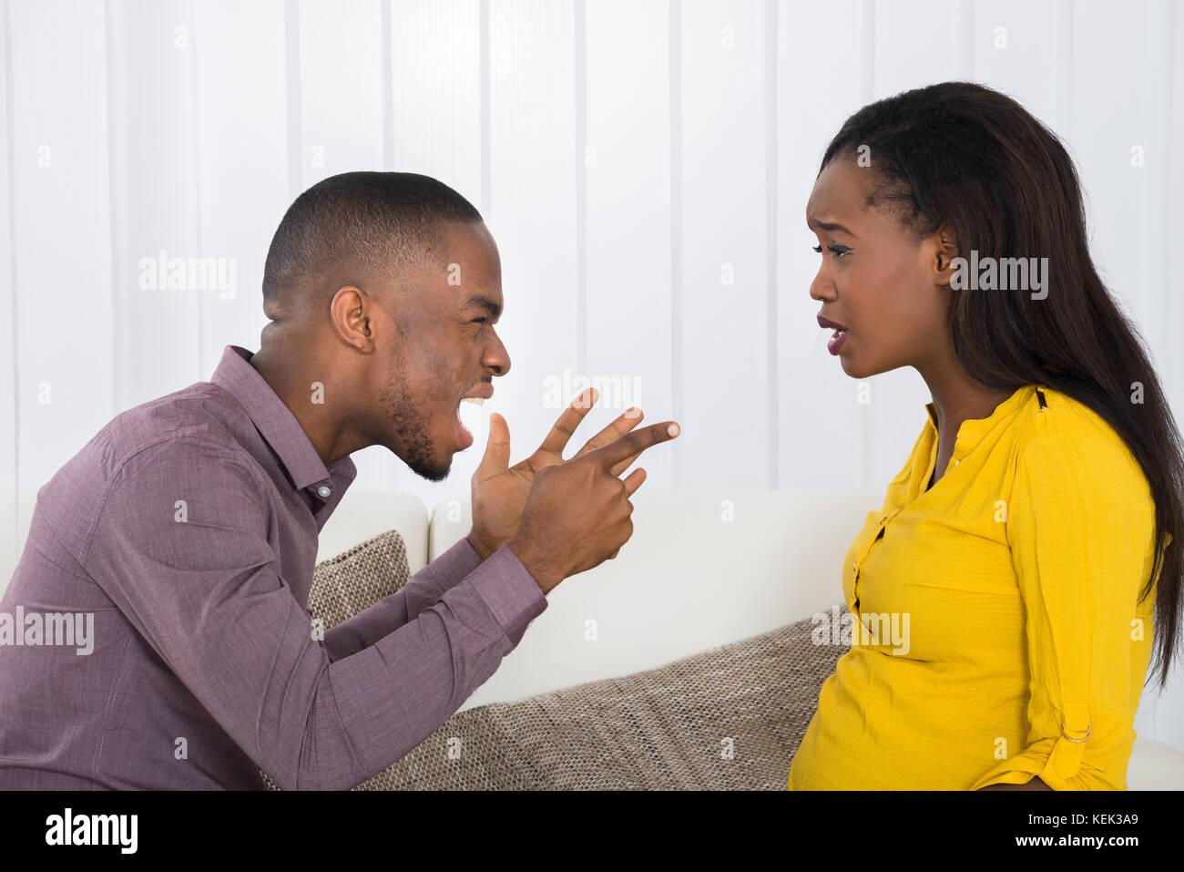 Arrabbiato giovane africano urlando al donna Immagini Stock