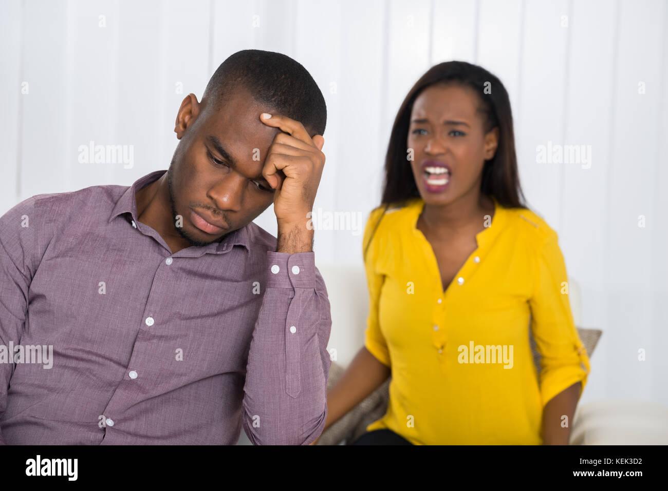 Infelice giovane donna avente argomento con uomo a casa Foto Stock