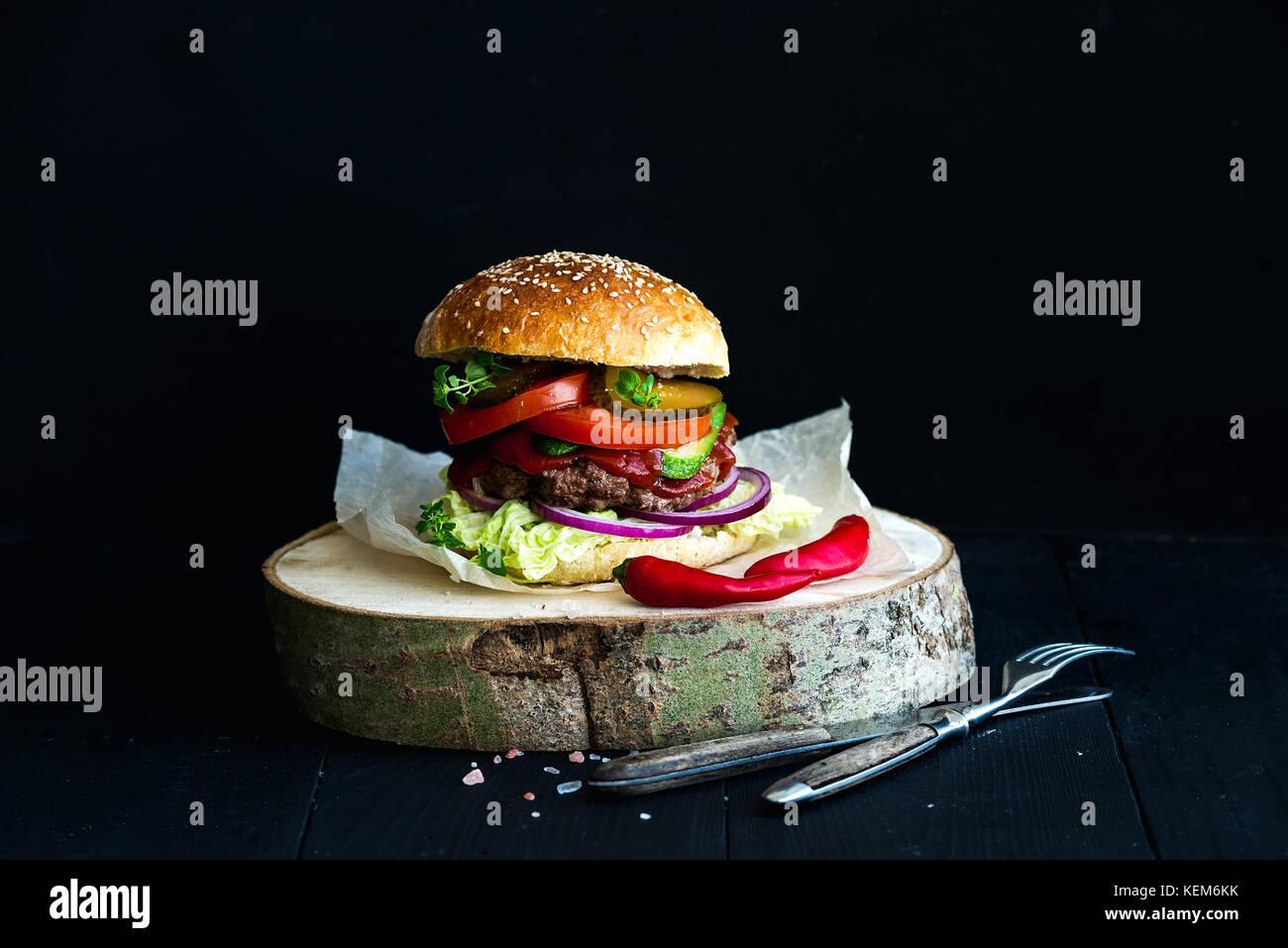 Freschi Fatti in casa burger su legno scheda servente con il piccante salsa di pomodoro, sale marino ed erbe su Immagini Stock