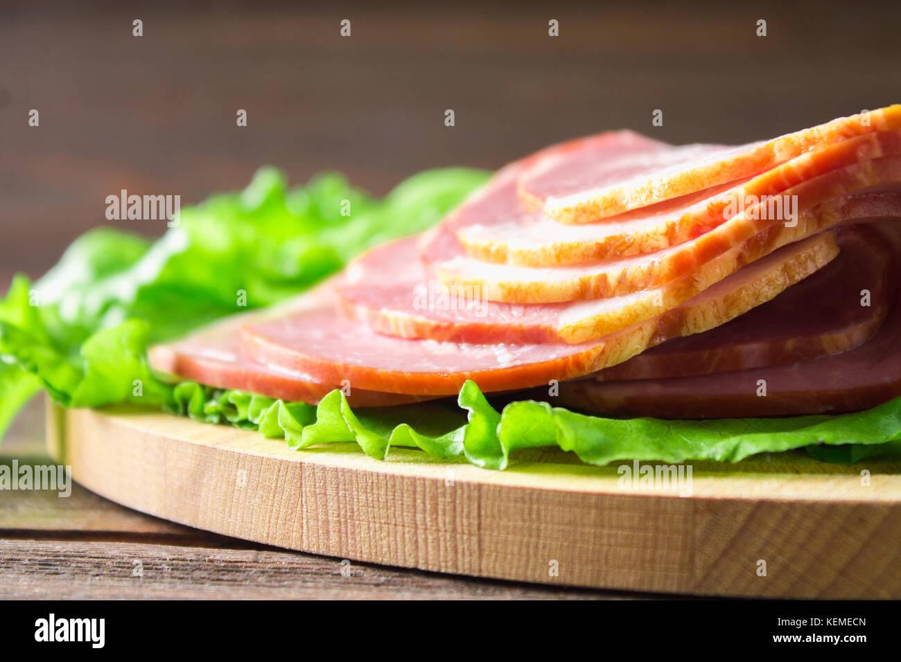 Fette di prosciutto crudo con fresco verde foglie di lattuga su un round tagliere. i prodotti a base di carne su Immagini Stock