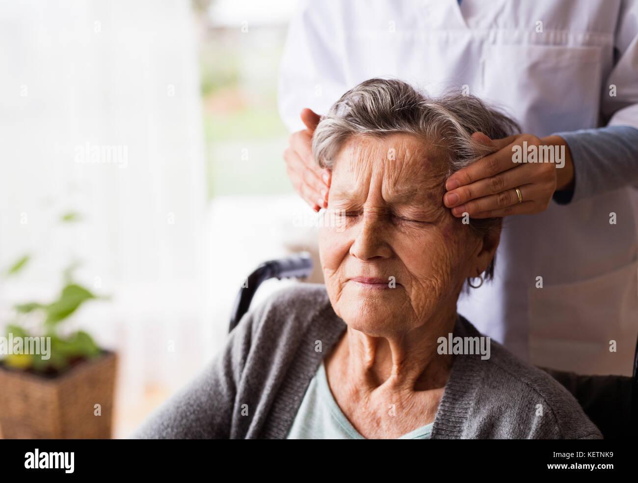 Salute e visitatori un senior donna durante la visita iniziale. Immagini Stock